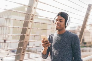 Guy on the street wearing headphones looking at his phone