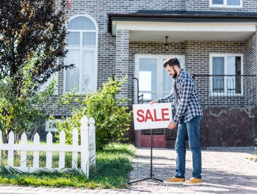 man placing for sale sign in front of house