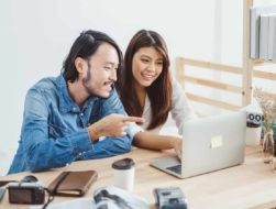 couple smiling and pointing at laptop screen