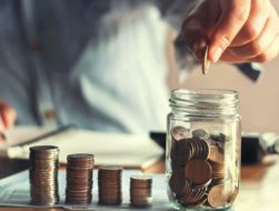 man putting coins in a jar