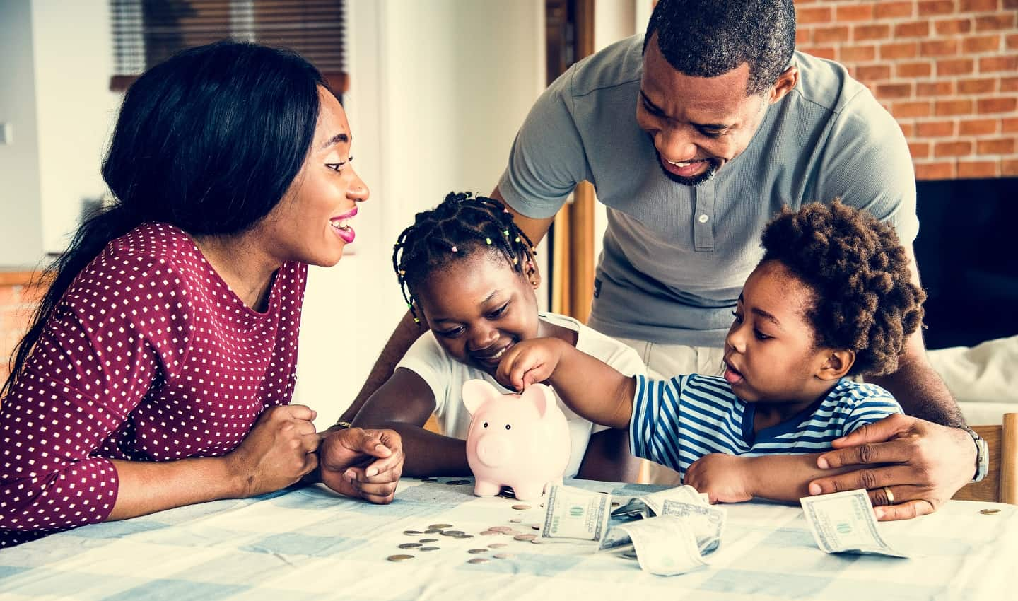 african american family sitting at table counting money in a piggy bank