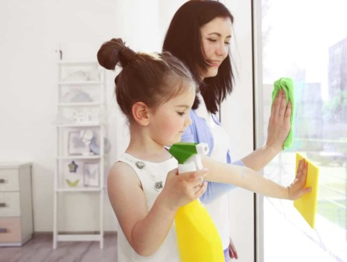 mom and daughter washing windows together