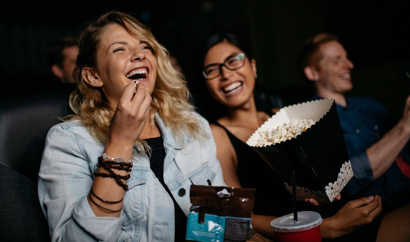 two girls laughing while watching a movie