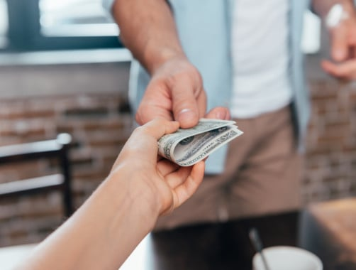 person lending cash to another person