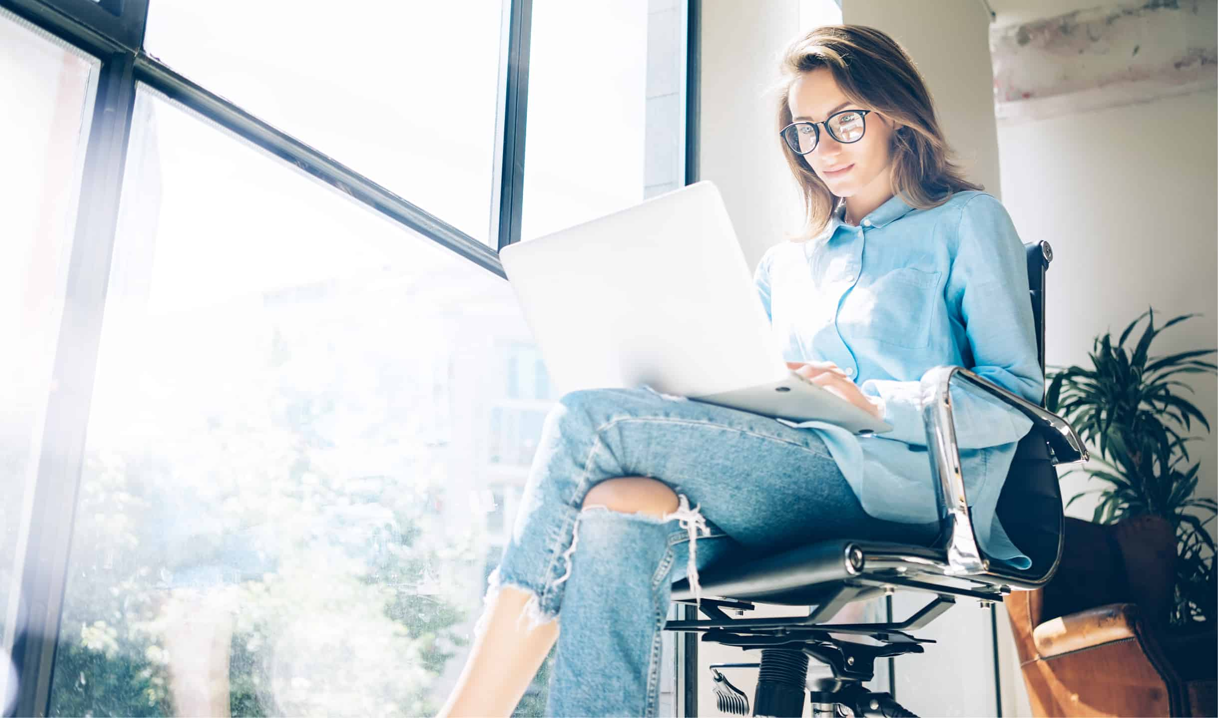 woman wearing glasses working on her laptop