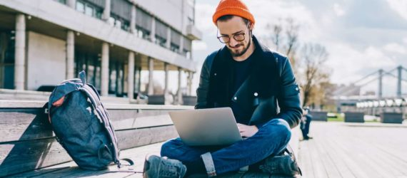 young man sitting on ground with backpack and laptop