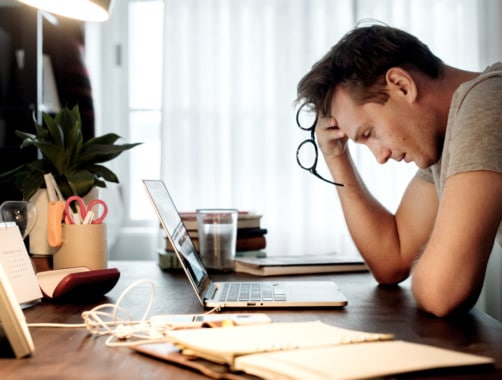 Man working on his laptop and showing visible signs of stress