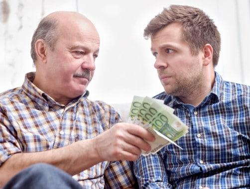 elderly man lending money to his adult son