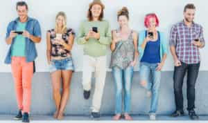 young people standing against a wall and looking at their phones