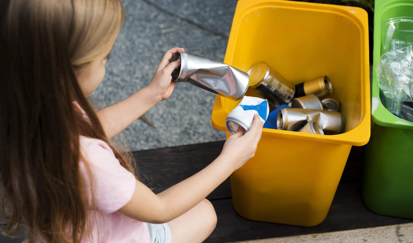 young girl recycling cans