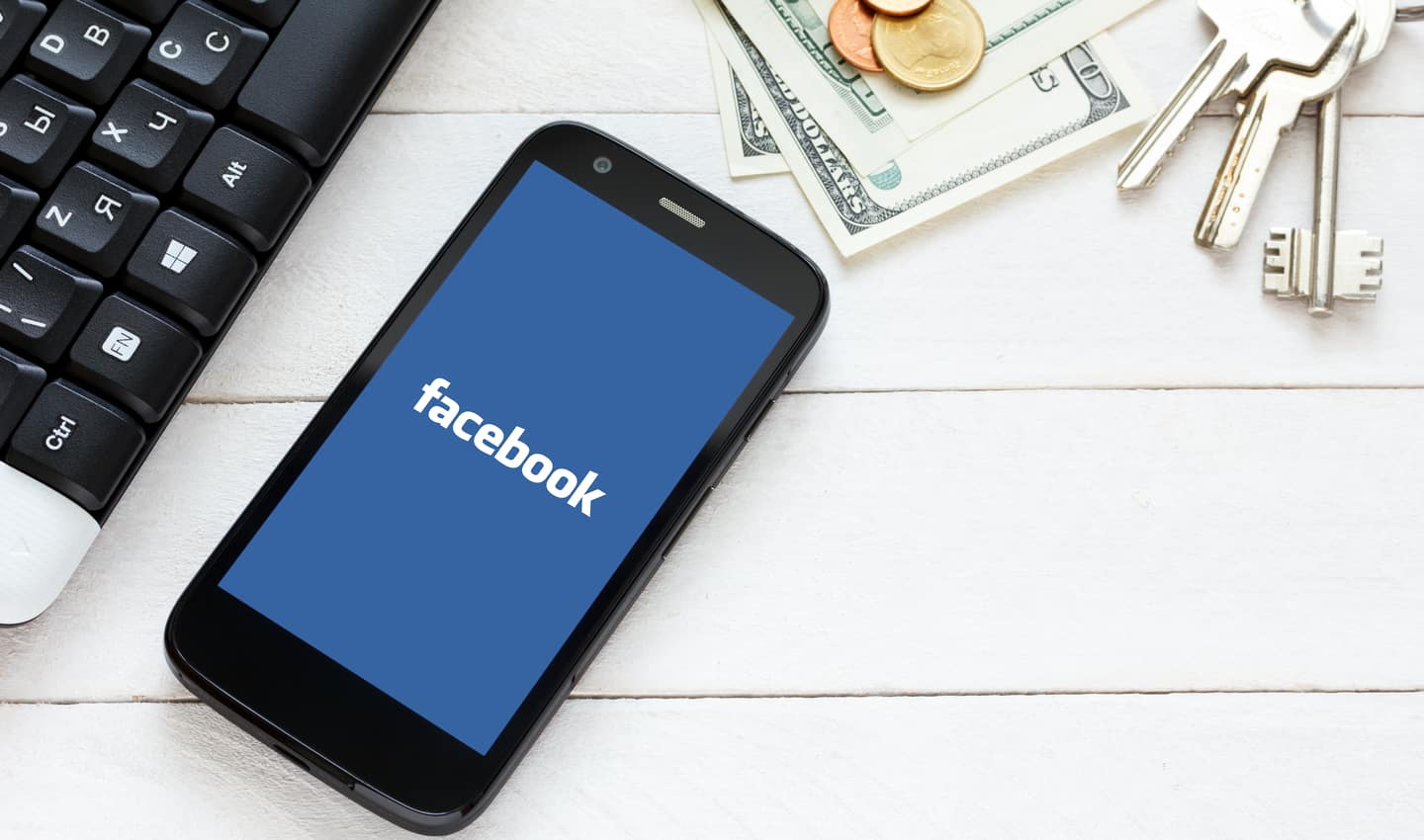 Facebook on mobile screen next to cash