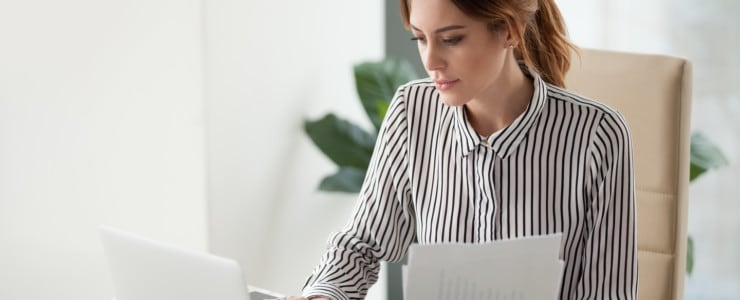 woman sorting through finances on paper and laptop