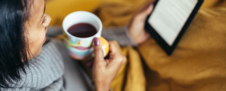 woman reading ebook while sipping coffee