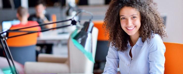 woman sitting at work desk smiling
