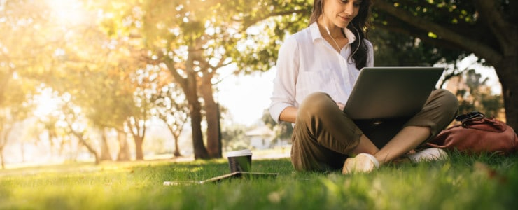 woman sitting on grass working on a laptop