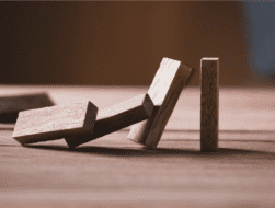 Jenga pieces falling like dominos as an illustration of risk