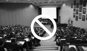 Black and white photo of a college classroom with caution symbol overlayed