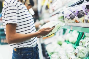 woman looking at her phone in grocery aisle