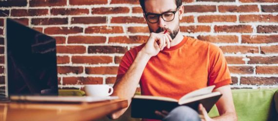 man reading a book about how to get out of debt