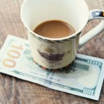 coffee cup setting on 100 dollar bill