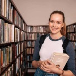 woman holding books in library